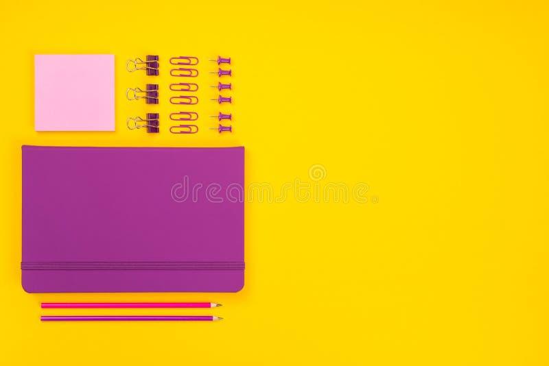 Draufsicht des violetten Notizbuches, der Bleistifte, der Clip, der Klammern, der Anmerkung und der anderer stationär Schulzusätz stockbild