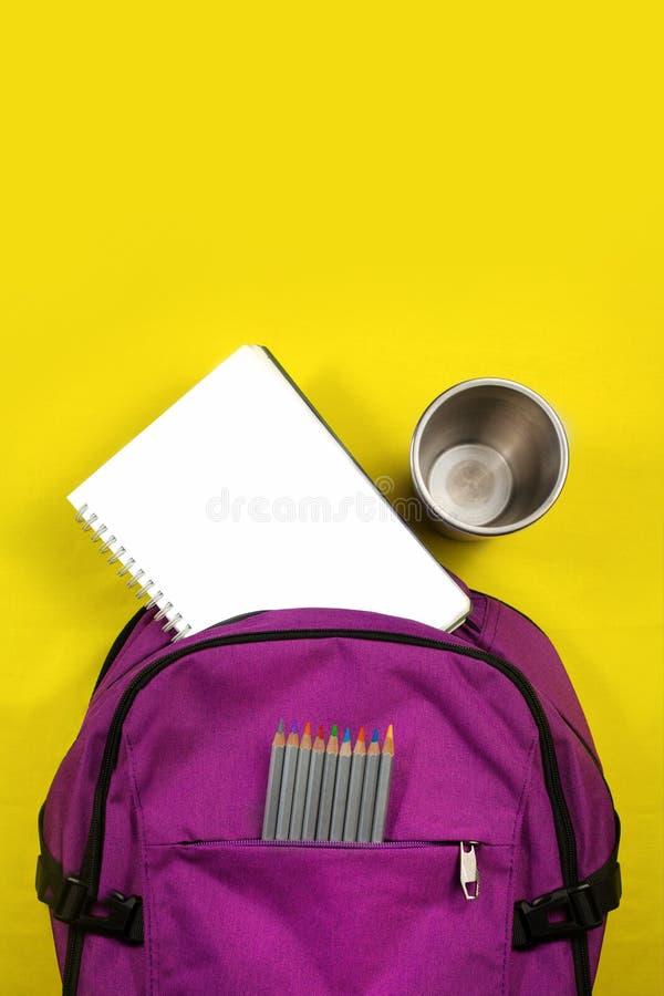 Draufsicht des violetten Rucksacks über einen gelben Hintergrund, Bleistifte, Notizblock, Satz für Kreativität, Briefpapier für S lizenzfreie stockbilder