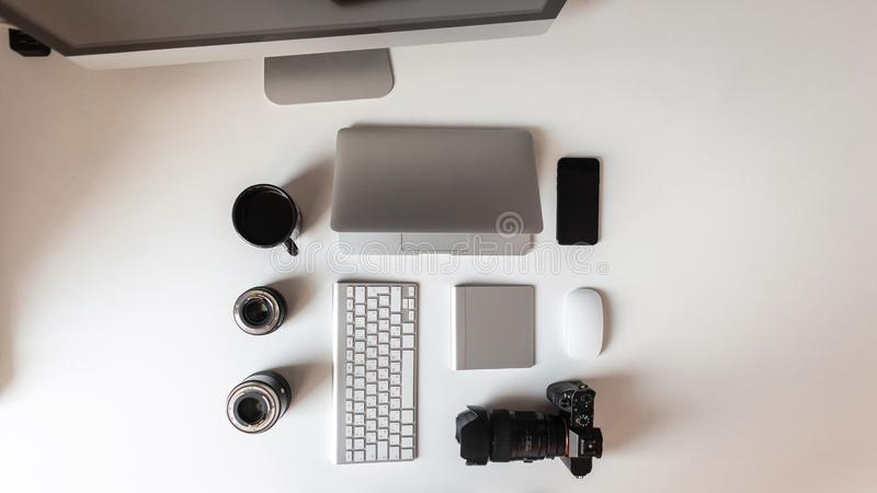 Draufsicht des weißen Desktops, der einen Laptop hat, Linsen für die Kamera, eine moderne Berufskamera, ein schwarzer Tasse Kaffe lizenzfreies stockbild