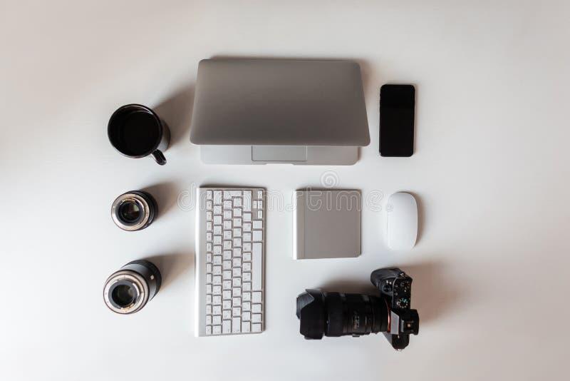 Draufsicht des weißen Desktops, der einen Laptop hat, Linsen für die Kamera, eine moderne Berufskamera, ein Tasse Kaffee, Tastatu stockbild