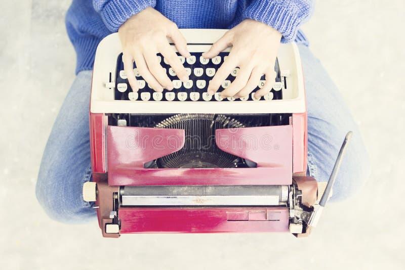 Draufsicht einer Frau, die auf dem Boden und der Schreibenschreibmaschine sitzt stockfotos
