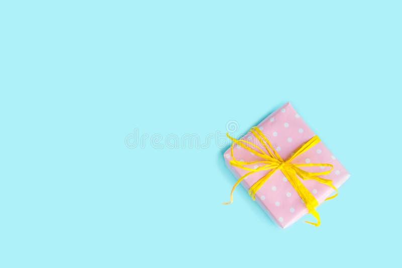 Draufsicht einer Geschenkbox, die im Rosa eingewickelt wurde, punktierte Papier und band gelben Bogen über hellblauem Hintergrund stockbild