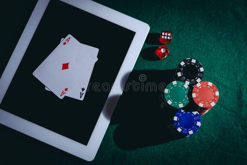 Draufsicht einer grünen Schürhakentabelle mit Tablette, bricht ab und würfelt Spielendes on-line-Konzept lizenzfreie stockfotografie
