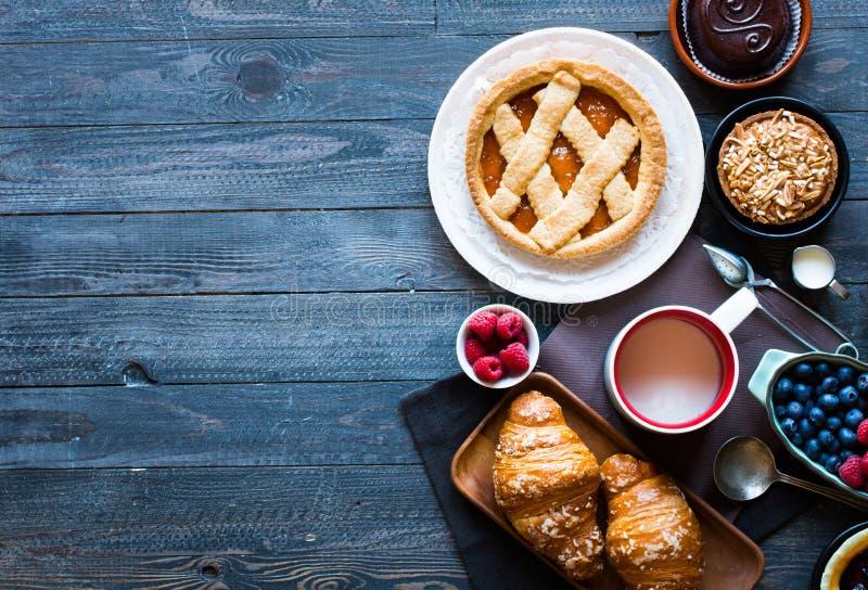 Draufsicht einer hölzernen Tabelle voll der Kuchen, Früchte, Kaffee, Kekse lizenzfreies stockfoto