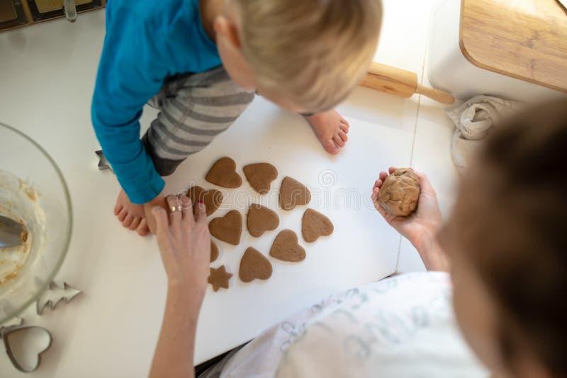 Draufsicht einer Mutter und ihres Kleinkindkindes, die Herz machen, formte Plätzchen lizenzfreie stockbilder