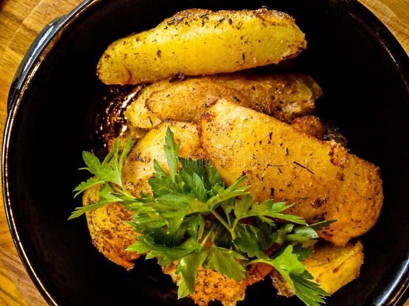 Draufsicht einer Ofenkartoffel in einem Tongefäß Schwarze keramische Schüssel mit appetitanregenden Ofenkartoffeln stockfotografie