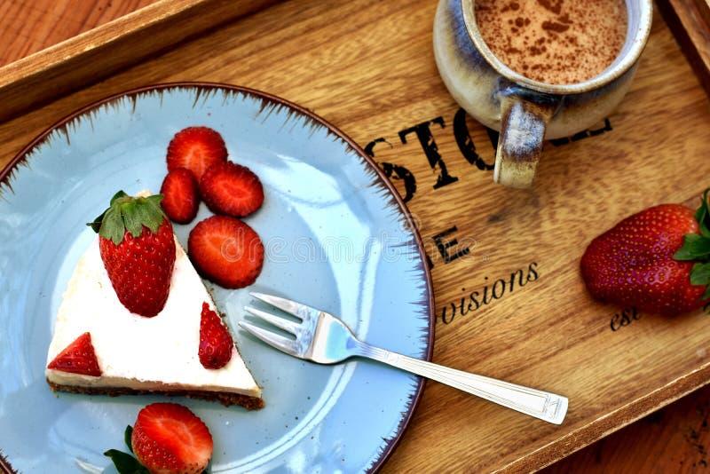 Draufsicht einer Scheibe des rohen weißen Erdbeerkuchens auf einer blauen Platte stockfotos