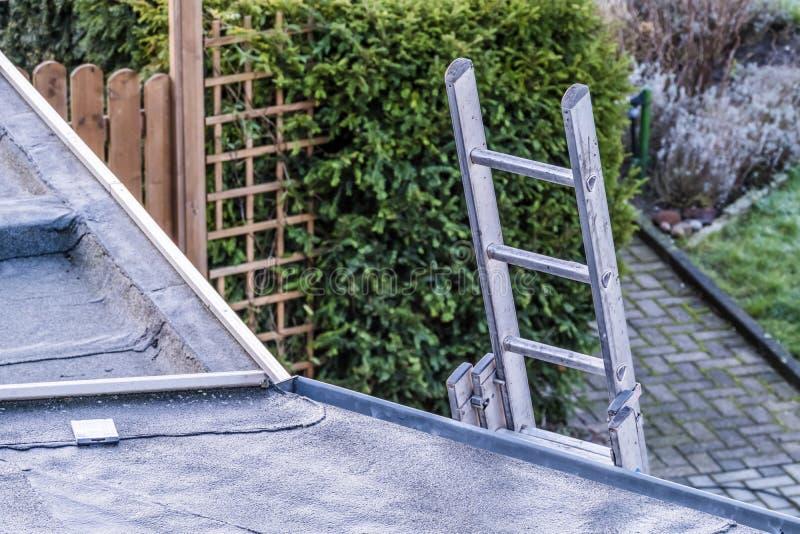 Draufsicht einer silbernen Aluminiumleiter, die an der Wand des Hauses sich lehnt stockfotos
