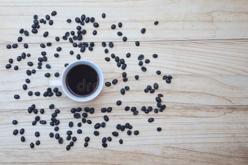 Draufsicht einer weißen Schale neuen coffe auf einem hölzernen Hintergrund mit Kaffeebohnen stockfoto