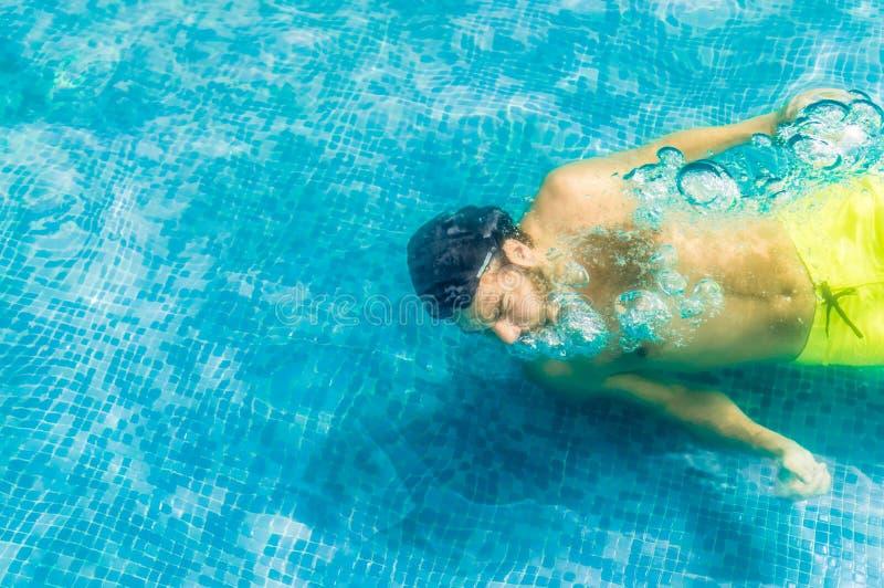 Draufsicht eines jungen Mannes, der unter Wasser in Swimmingpool schwimmt lizenzfreies stockfoto