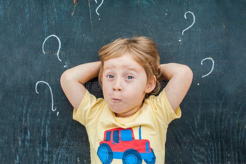 Draufsicht eines kleinen blonden Kinderjungen mit Fragezeichen auf Tafel Konzept für Verwirrung, Brainstorming und Wahl stockfotografie