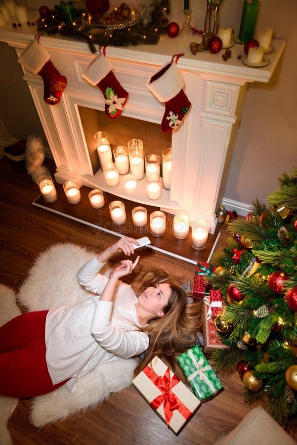 Draufsicht eines Mädchens, das unter einem Weihnachtsbaum liegt stockbilder
