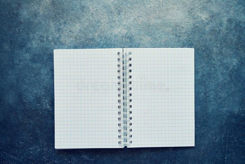 Draufsicht eines offenen Notizbuches mit leeren quadratischen Seiten Schulnotizbuch auf einem blauen Hintergrund, gewundener Noti lizenzfreie stockbilder