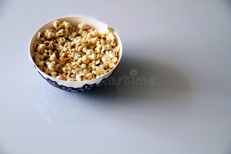 Draufsicht eines Stapels des Popcornkaramelpopcorns in einer Platte auf einem Glastisch stockbilder