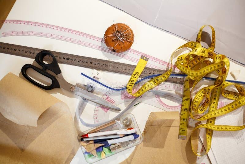 Draufsicht eines Zentimetergelbs, der Scheren, des Machthabers und anderer Werkzeuge der Näherin Herstellung von Kleidung Arbeits lizenzfreies stockbild