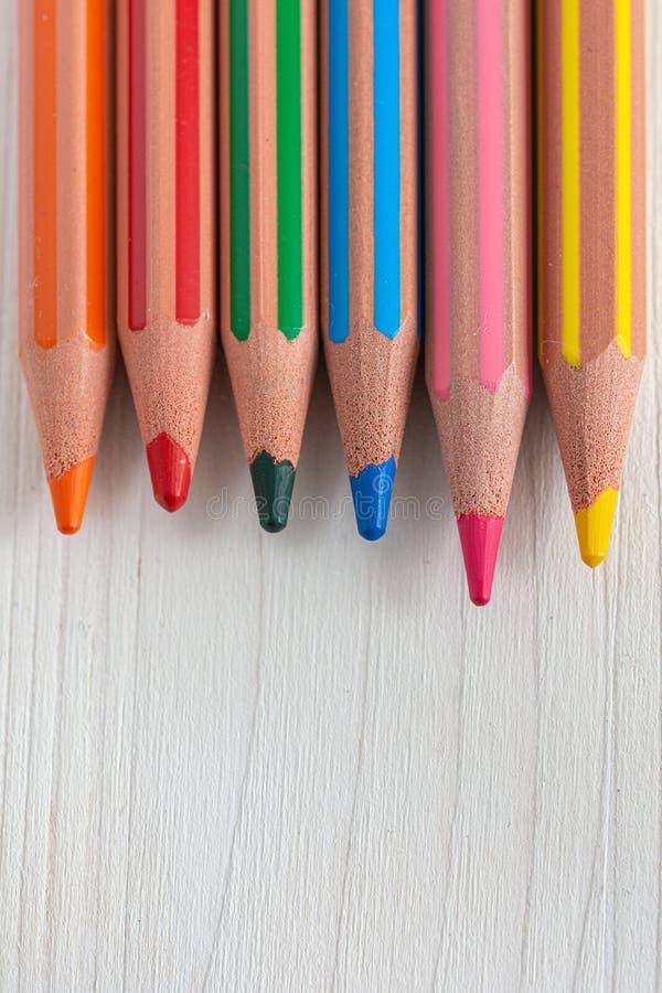 Draufsicht einiger farbiger Bleistifte für die Schule sortiert auf weißem hölzernem Hintergrund lizenzfreie stockbilder