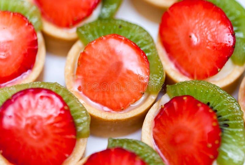 Draufsicht für Gruppe Minitörtchen mit Scheiben der Erdbeere und der Kiwi stockfoto