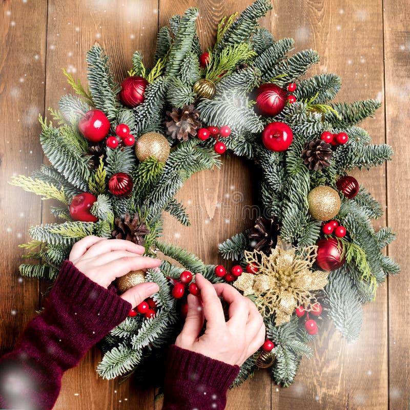 Draufsicht-Frau-Handfloristen-Hand Making Christmas-Kranz auf Holztisch-hölzernem Hintergrund-Schnee-Quadrat stockfoto