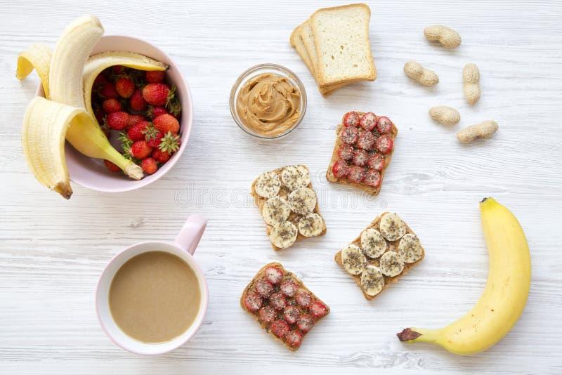 Draufsicht, gesundes Frühstück: Latte, strenger Vegetarier röstet mit Früchten, Samen, Erdnussbutter Weißer hölzerner Hintergrund stockfoto