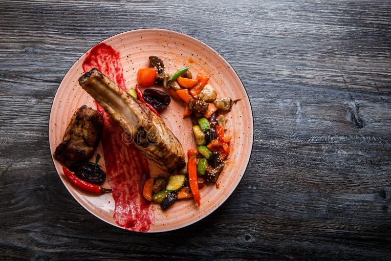 Draufsicht großes geschmackvolles Stück der gegrillten Rippe mit Fleischsteak mit gegrilltem Gemüse stockbild