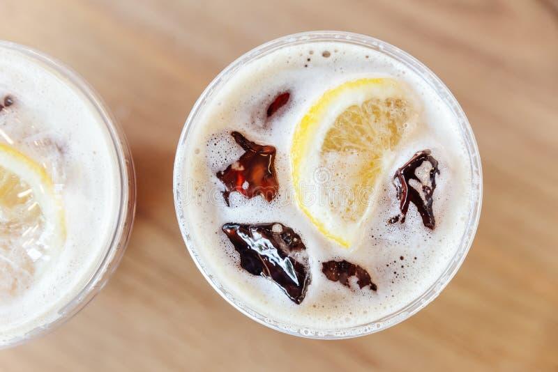Draufsicht Iced des kalten Gebräunitrokaffees mit Zitrone auf Holztisch stockfoto