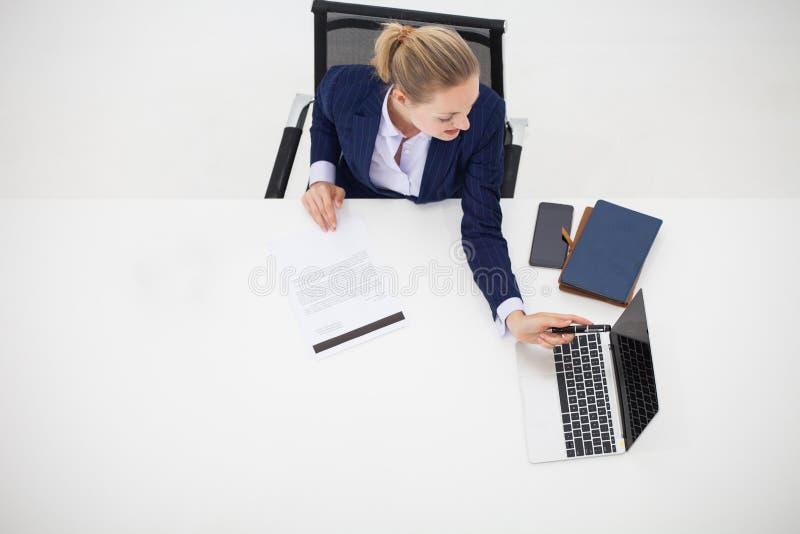 Draufsicht, junge Geschäftsfrau, die an Bürode sitzt und arbeitet lizenzfreies stockbild