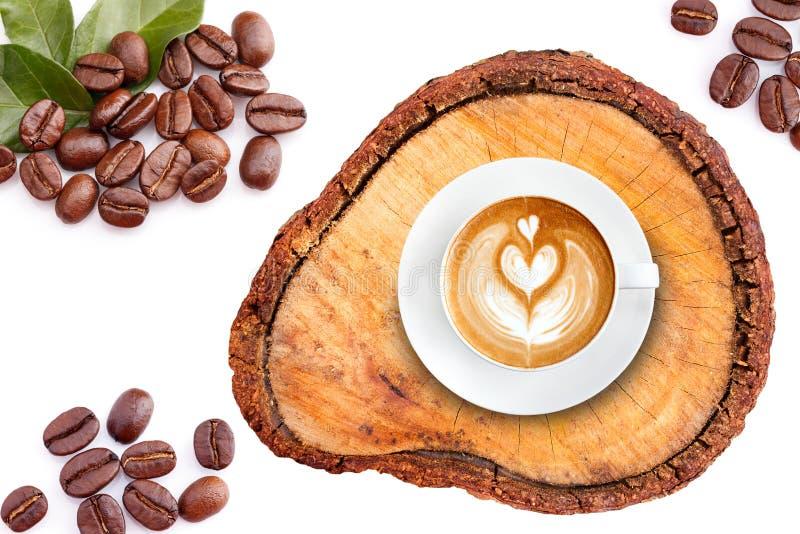 Draufsicht Lattekunstkaffee auf Holz mit Röstkaffeebohnen stockfotografie