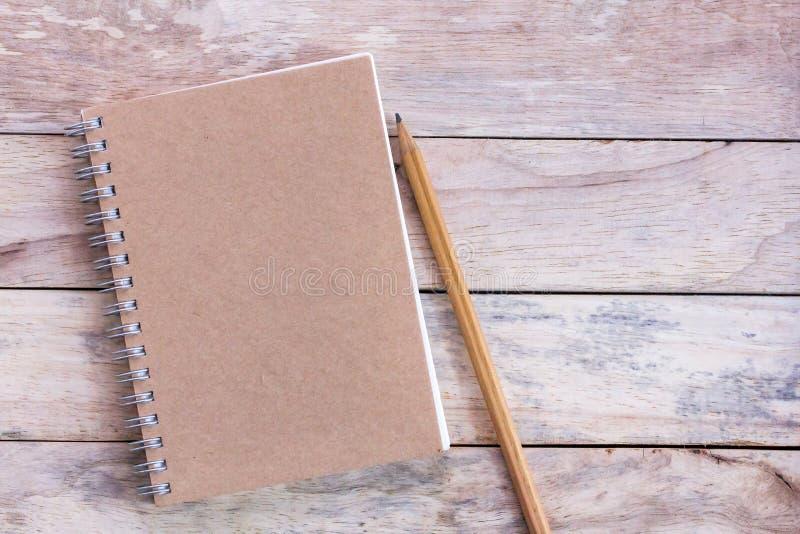 Draufsicht mit leerem leerem Notizblock und Bleistift auf hölzerner Tabelle lizenzfreie stockfotografie