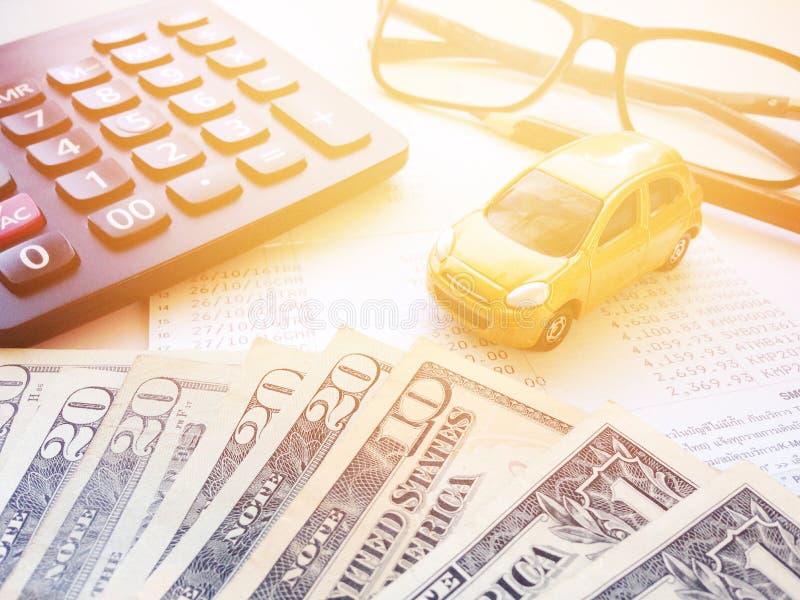Draufsicht oder flache Lage des Miniatur- Automodells, der amerikanischen Dollar Bargeld, des Taschenrechners und des Sparkontobu stockbild