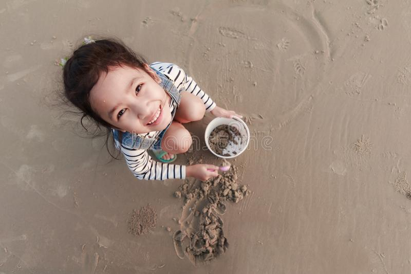 Draufsicht portriat asiatisches kleines Mädchen, das auf den Sandstrand wi spielt lizenzfreie stockfotos