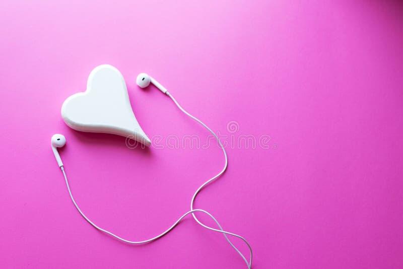 Draufsicht reizende Nahaufnahme von weißen Kopfhörern auf Rosapastellplastikbeschaffenheitshintergrund Pastellfarbkonzept, minima lizenzfreie stockfotos