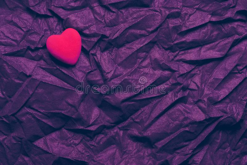 Draufsicht-rotes Herz auf geknittertem dunklem purpurrotem Beschaffenheits-Hintergrund Glücklicher Valentinstag und Liebes-Konzep stockfoto