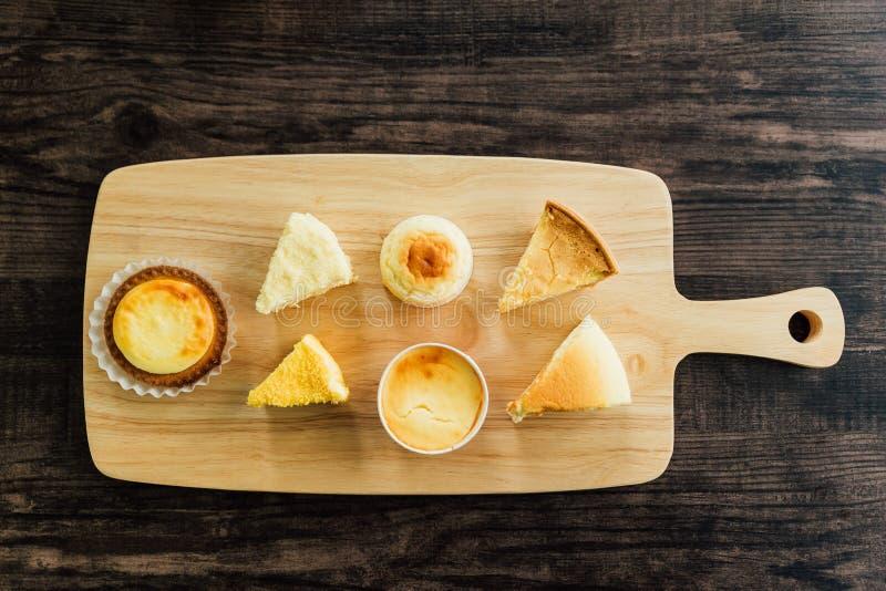 Draufsicht viele Arten Mascarpone-crème gebrannte Käsekuchenscheiben, Käse-Törtchen auf hölzernem hackendem Brett, glatter, reich stockbild
