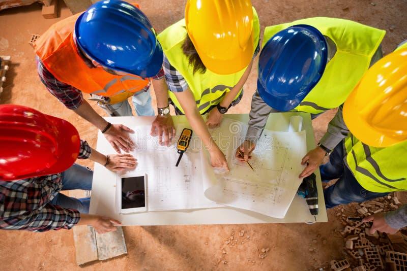 Draufsicht von Architekten überprüfen Blaupause, wenn Bau geht stockfotos