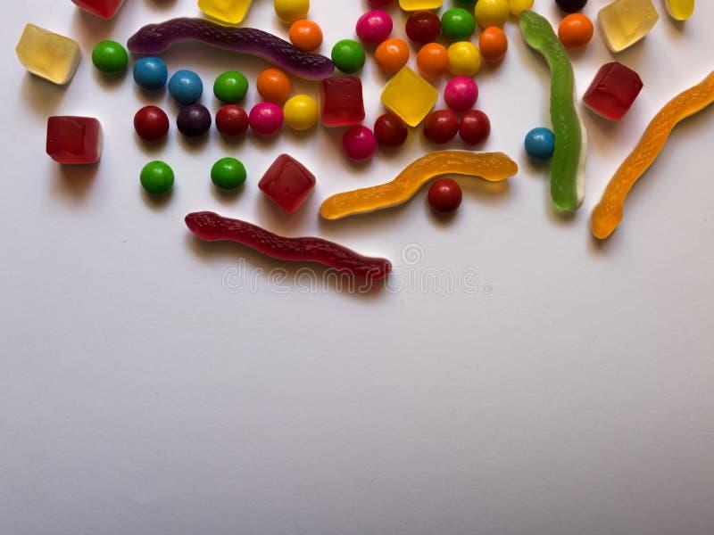 Draufsicht von bunten harten und Geleesüßigkeiten auf weißem Hintergrund mit Kopienraum stockfotografie