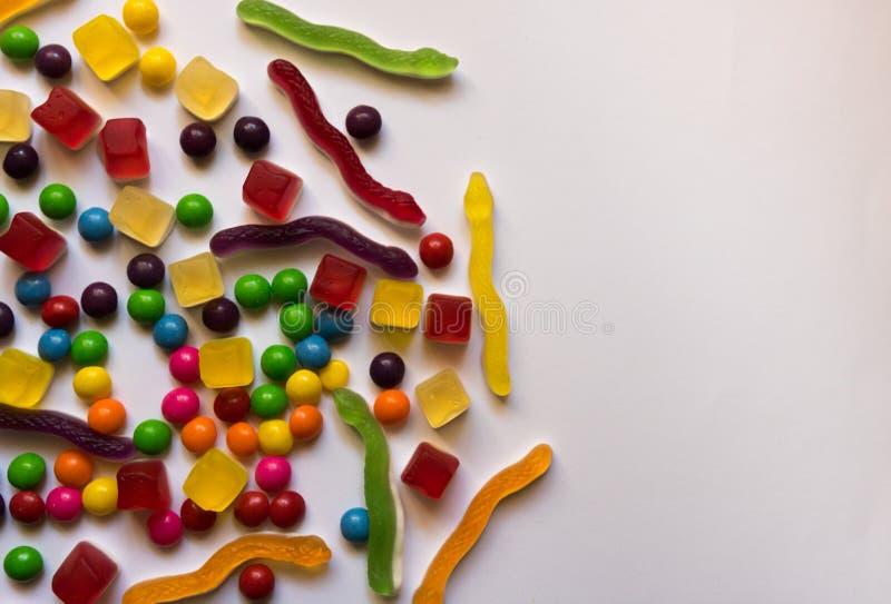 Draufsicht von bunten harten und Geleesüßigkeiten auf weißem Hintergrund mit Kopienraum stockbild