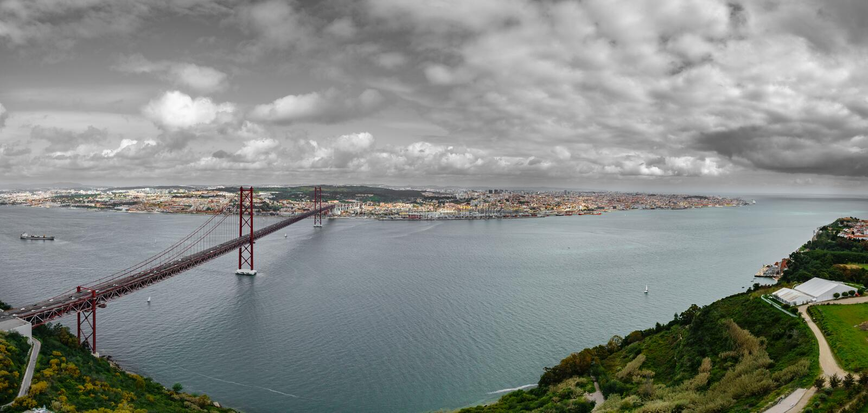 Draufsicht von 25 De Abril Bridge und Lissabon gegen schwarzen Himmel stockfotos