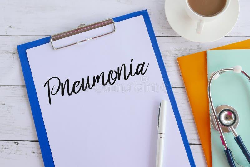Draufsicht von den Büchern, von Kaffee, von Stift, von Stethoskop, von Klemmbrett und von Papier geschrieben mit Pneumonie Gesund stockfotos