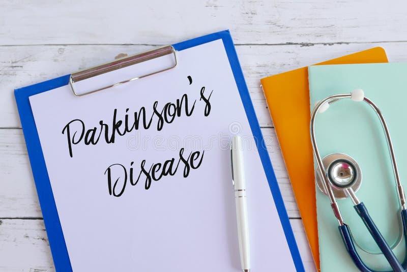 Draufsicht von den Büchern, von Stethoskop, von Stift, von Klemmbrett und von Papier geschrieben mit Parkinson' s-Krankheit  stockfoto