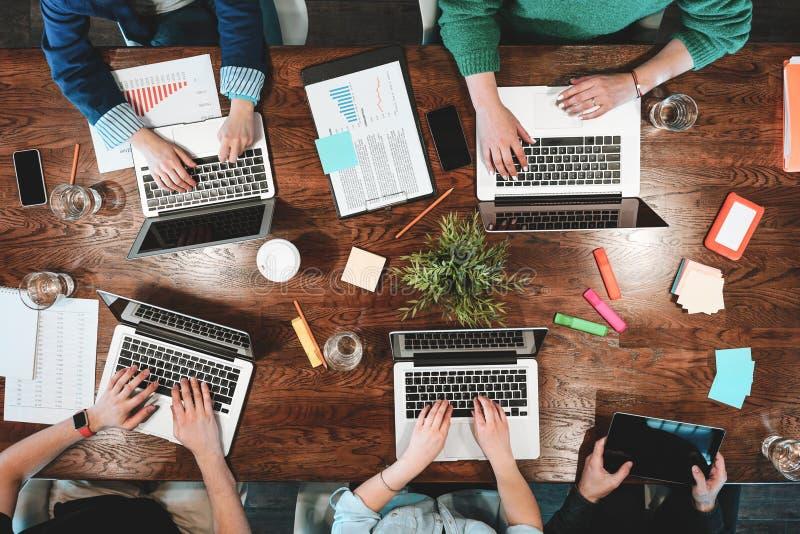 Draufsicht von den coworking Leuten, die zusammen um Tabelle sitzen Geschäftstreffen von jungen kreativen Hippies lizenzfreie stockfotografie