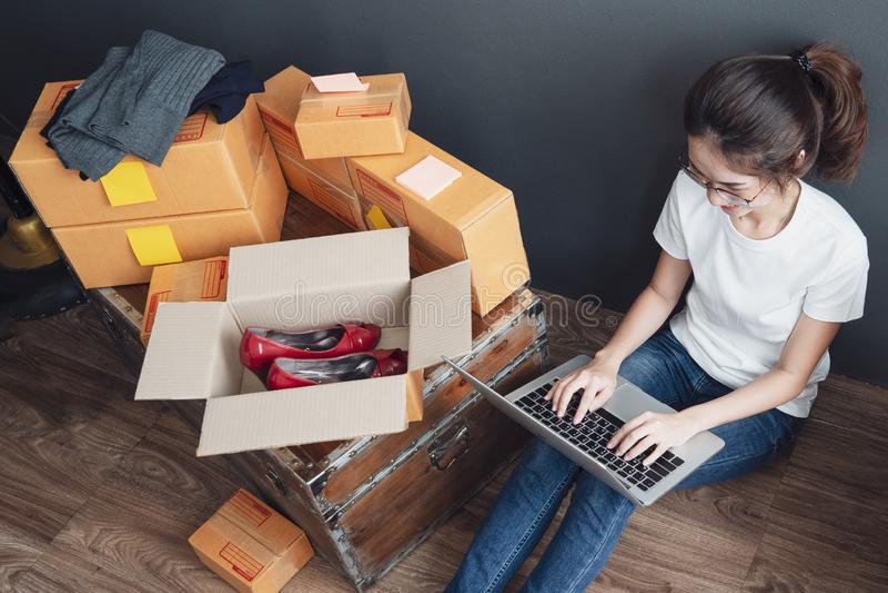 Draufsicht von den Frauen, die Laptop-Computer vom Haus auf Bretterboden mit Postpaket, on-line-Ideenkonzept verkaufend Arbeits s lizenzfreies stockbild