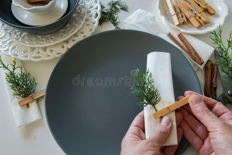 Draufsicht von den Frauenhänden, welche die Tabelle für Winterurlaube vorbereiten und vereinbaren Winterdekoration stockfotografie