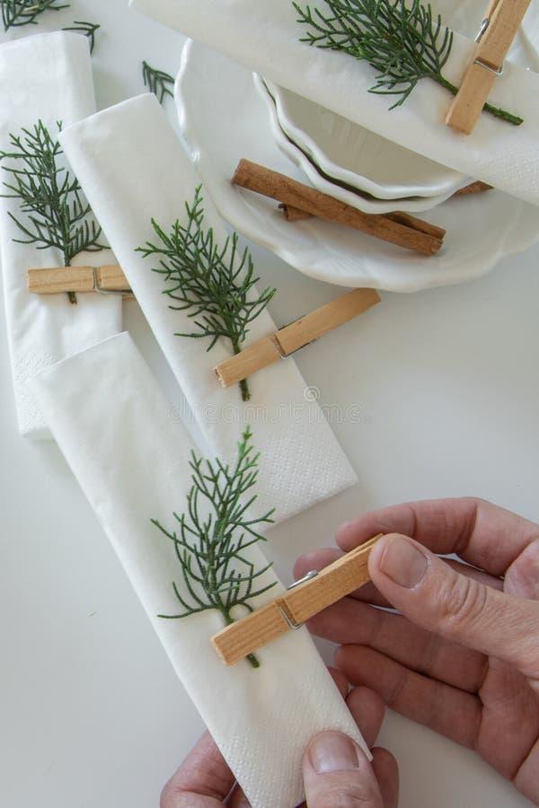 Draufsicht von den Frauenhänden, welche die Tabelle für Winterurlaube vorbereiten und vereinbaren Winterdekoration stockfotos
