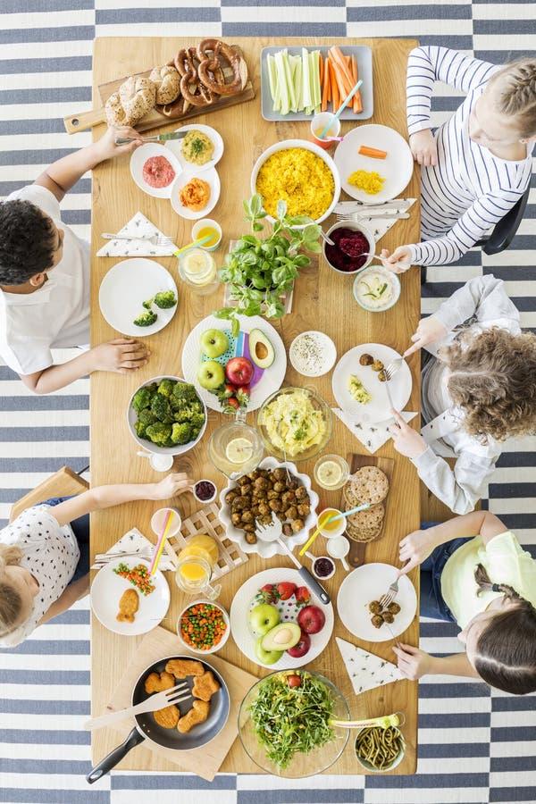 Draufsicht von den Kindern, die gesunde selbst gemachte Mahlzeit essen Hölzerne Tabelle stockbild