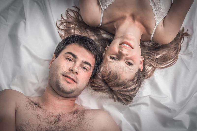 Draufsicht von den liebevollen Paaren, die zusammen im Bett liegen stockfoto