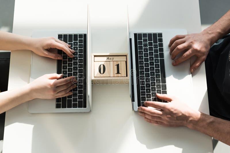 Draufsicht von den männlichen und weiblichen Händen, die auf Laptops mit hölzernem drucken stockfoto