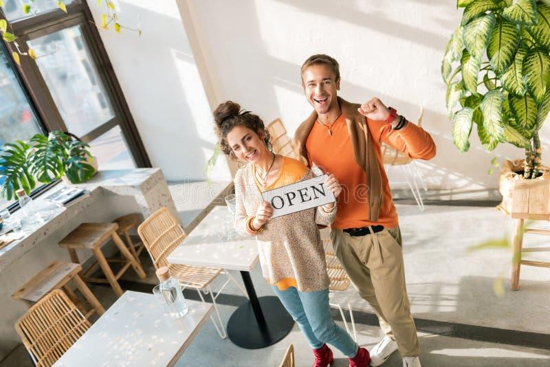 Draufsicht von den stilvollen schönen Paaren, die in ihrem eigenen Restaurant stehen stockfoto