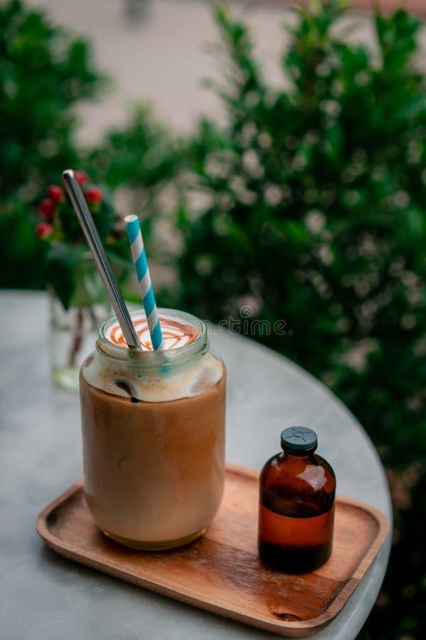 Draufsicht von den trockenen Blumen, die an Tischplatte im Café mit glas des flach-weißen Kaffees nahe einigen Blumen verzieren lizenzfreies stockfoto