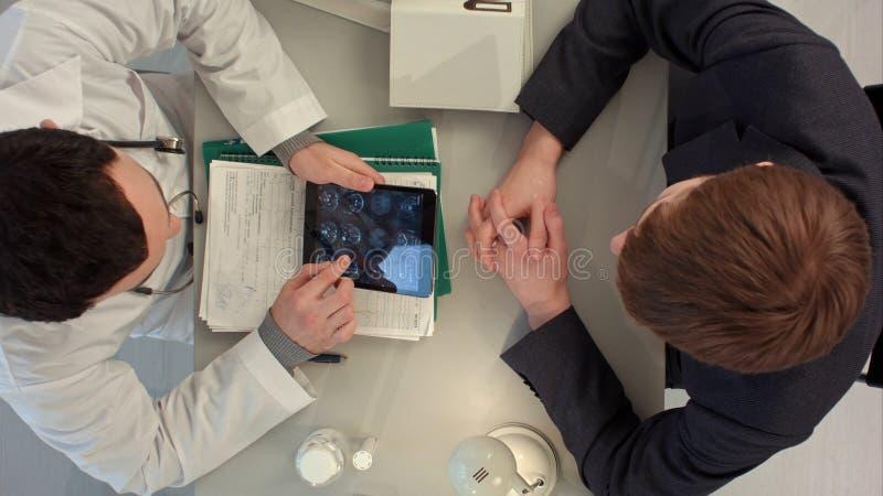 Draufsicht von Doktor Röntgenstrahl mit Patienten wiederholend stockfotos