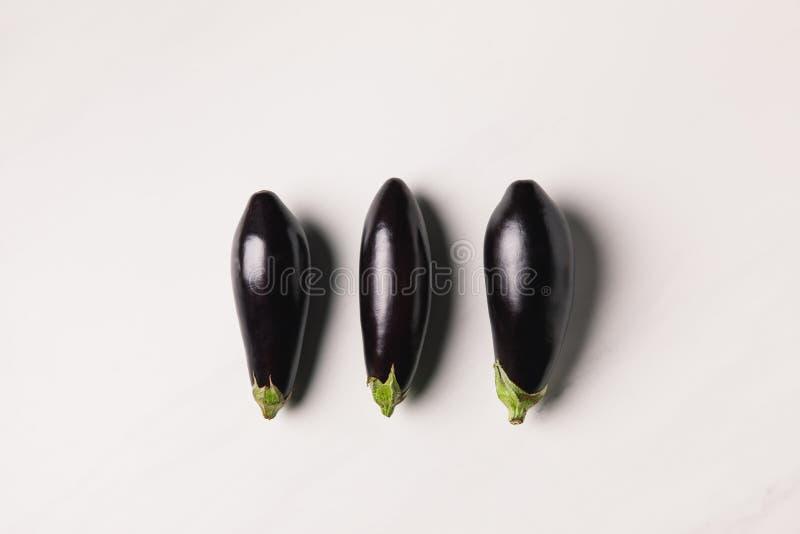 Draufsicht von drei Auberginen auf weißer Oberfläche stockfotos